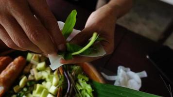 mano de mujer asiática envolviendo envolturas de albóndigas vietnamitas o ban hoi. video