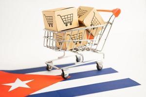 caja con logotipo de carrito de compras y bandera de cuba, importación y exportación en línea foto