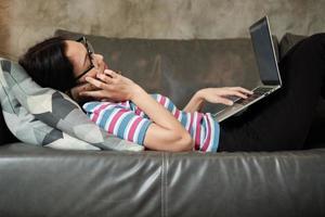 mujer asiática trabajando en casa, acostada y usando un teléfono móvil. foto