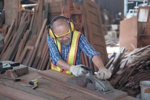 Carpintero masculino senior está trabajando en una fábrica de aserraderos de madera. foto