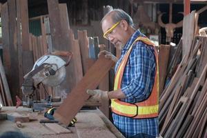 Carpintero asiático senior cortando madera en la fábrica. foto