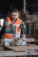 Joven carpintero caucásico está trabajando en una fábrica de muebles de madera, foto
