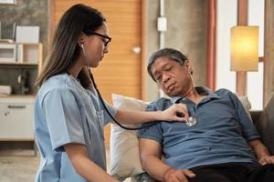 Female doctor checking health of  Asian elderly male patient at home. photo