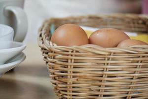 huevos frescos orgánicos en canasta tejida, tazas blancas sobre una mesa de madera. foto