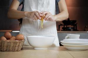 cocinera con un delantal blanco está rompiendo un huevo en la cocina de casa. foto