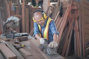 un viejo carpintero asiático trabaja en una fábrica de madera. foto