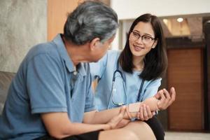 médico terapeuta examina paciente anciano en casa. foto