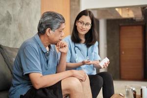 atención médica domiciliaria, doctora ayudando a un paciente masculino a tomar medicamentos foto