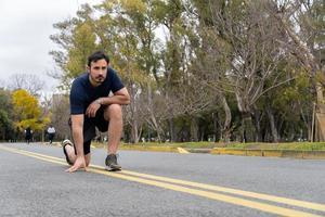 El hombre se prepara para trotar en el parque, vista al ras foto