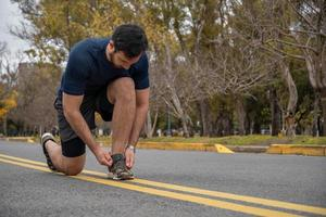 sporty man tying his shoelaces while exercising outdoors photo
