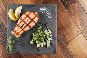 Salmon fish steak with lemon and greens photo