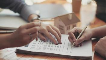 Cropped image of real estate agent assisting client to sign contract photo