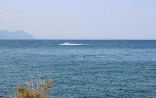 Seascape with mountains and people on a jet ski photo