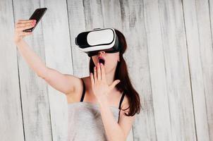 Chica guapa con gafas de realidad virtual, sosteniendo su teléfono frente a su cara foto