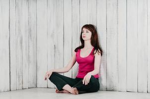 chica en top rosa, sentada con las piernas cruzadas en el suelo, fondo claro foto