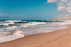 Paradise ocean beach, footprints in wet sand, distant hotels photo