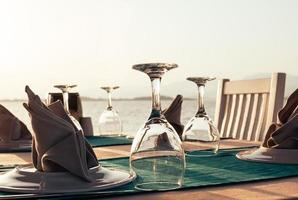table setting at beach restaurant at sunset photo