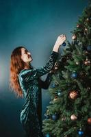 Atractiva mujer sonriente decorando el árbol de navidad foto