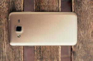 closeup of champagne color smart phone, on wooden table, top view photo