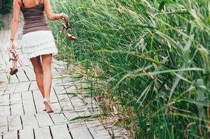 slim barefoot girl, high heels in hands, walking away photo