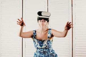 Mujer rubia con gafas de realidad virtual, apuntando sus manos en el aire foto
