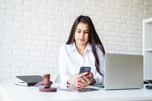 Retrato de joven abogada en su lugar de trabajo usando su teléfono foto