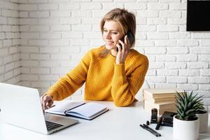 Mujer joven en suéter amarillo usando laptop y llamando por teléfono foto