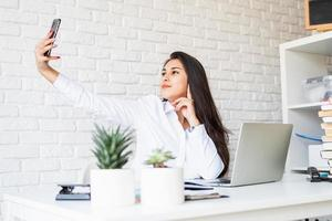Young latin woman in white shirt making selfie photo