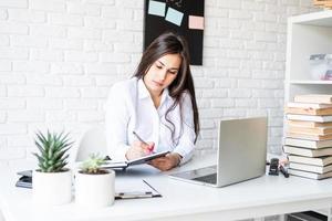 Young brunette teacher writing having online class photo