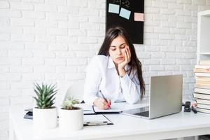 Young sad brunette teacher writing having online class photo
