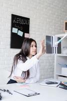 Young latin woman in white shirt teaching english online photo