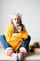 Funny young woman in yellow plaid sitting on the floor hugging her dog photo