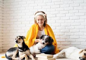 Funny young woman in yellow plaid sitting with her dogs reading a book photo