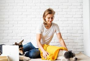 Funny young woman in yellow plaid sitting on the floor with her dogs photo