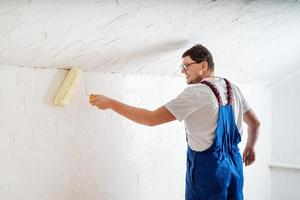 young man in blue overalls painting wall photo