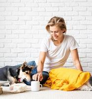 woman in yellow plaid sitting on the floor playing with her dogs photo