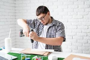 Young man making renewable energy project dummy using drill photo