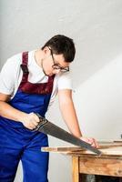 carpintero con un mono azul aserrando una tabla con una sierra de mano foto