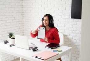 Joven mujer latina en auriculares negros enseñando inglés en línea foto