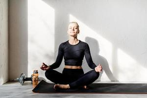 young blond woman doing yoga or meditating at home photo