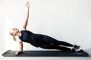 Young blond woman working out standing in plank position photo