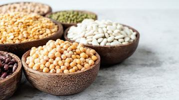 Various dried legumes in wooden bowls on white marble background photo