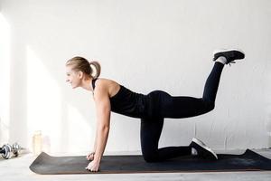 Joven mujer rubia trabajando haciendo ejercicios de glúteos foto