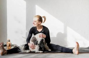 Happy young blond woman patting her dog at the home gym photo