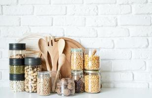 Various dried legumes in glass jars on white marble background photo