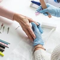 Manicure master in gloves using nail file to buff the nail of a client photo