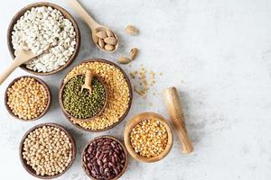legumes in wooden bowls top view flat lay on white marble background photo