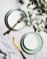 top view of dessert plates and cutlery with hard shadows photo