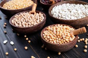 Various dried legumes in wooden bowls on wooden background photo