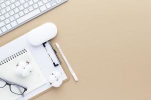 Vista superior de la mesa de escritorio de oficina con suministros de oficina, mesa beige foto